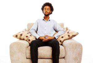 content young man sitting meditating in comfy chair