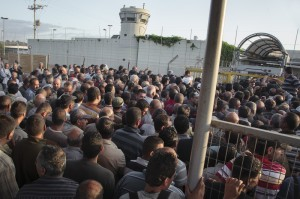Palestinians line up at an Israeli checkpoint electronicintifada.net